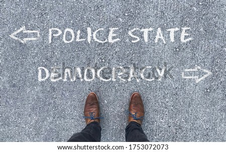 """Top view on a man standing in front of the words """"Police State"""" and """"Democracy"""" with arrows pointing to the left and right side of the picture"""
