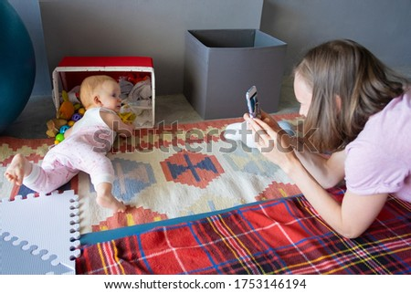 Young mom with smartphone taking picture of her curious baby daughter checking box with stuff, searching for her toys. Childhood or child care at home concept
