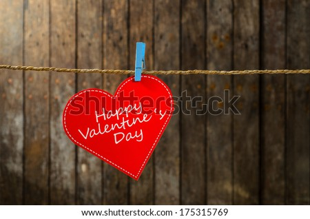 Cute big red heart hanging on the clothesline. On old wood background. #175315769