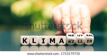 "Hand turns dice and changes the German expression ""klima killer"" ("" climate changer"") to ""klima neutral"" (""climate neutral""). Royalty-Free Stock Photo #1753179710"
