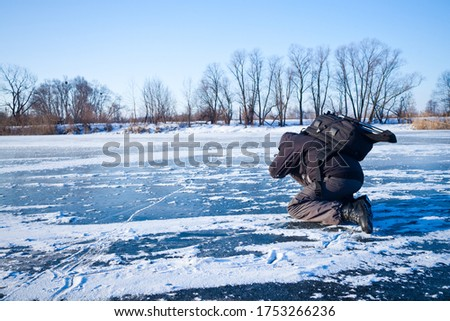 Man dressed in dark clothes taking pictures river that covered in ice and snow, photo outdoors
