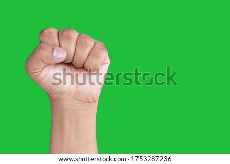 Hand of an Asian man forms Fist isolated on a green screen background.