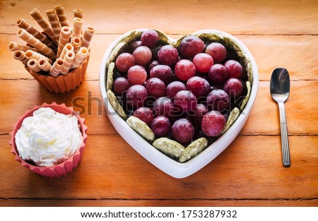 Close-up view of white heart-shaped plate full of red grapes, cream and biscuits. Wooden background #1753287932