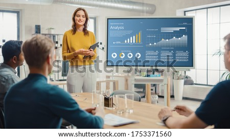 Female Chief Analyst Holds Meeting Presentation for a Team of Economists. She Shows Digital Interactive Whiteboard with Growth Analysis, Charts, Statistics and Data. People Work in Creative Office. Royalty-Free Stock Photo #1753371560