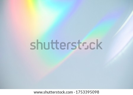 Blurred rainbow light refraction texture overlay effect for photo and mockups. Organic drop diagonal holographic flare on a white wall. Shadows for natural light effects #1753395098
