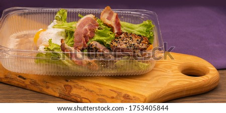 Closeup of salad with lettuce, tuna, bacon and egg in disposable plastic box. food delivered from a restaurant #1753405844