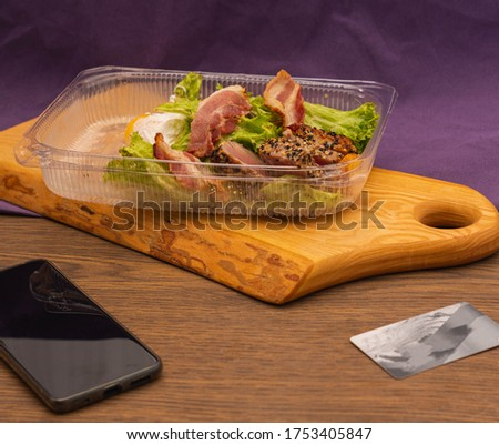 Salad with lettuce, tuna, bacon and egg in disposable plastic box. food delivered from a restaurant #1753405847