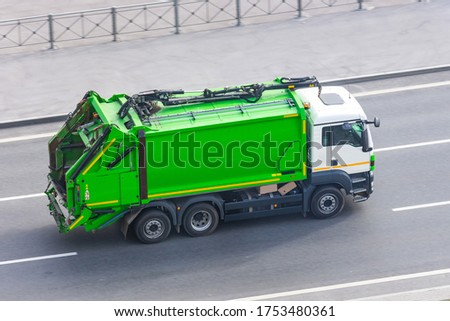 Truck for waste collection in residential areas of the city rides on the road Royalty-Free Stock Photo #1753480361