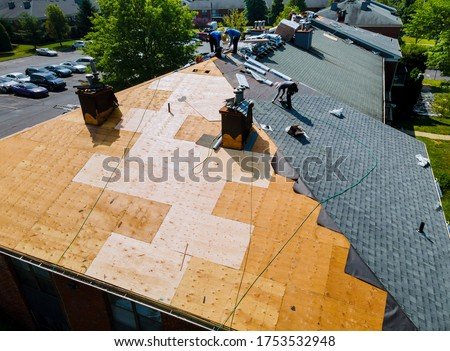 Roof repairs old roof replacement with new shingles of an apartment building Royalty-Free Stock Photo #1753532948
