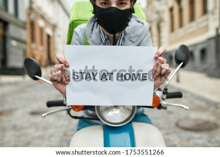 Young delivery woman in mask with thermo backpack holding a card with the inscription Stay at Home, delivering food on a motor scooter. Courier, delivery service, lockdown concept. Focus on card