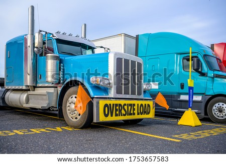 Blue powerful big rig classic semi truck with vertical pipes and oversize load sign on the bumper standing on the reserved spot on the truck stop beside another semi trucks with semi trailers