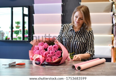 flower business. The florist makes a bouquet. The seller in floristic salon. Delivery of bouquets. #1753683599