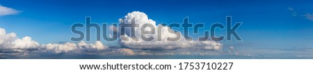 Panoramic View of Puffy White Clouds with Blue Sky during a beautiful Sunny Day. Taken over Vancouver, British Columbia, Canada. Royalty-Free Stock Photo #1753710227