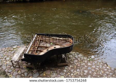 Broken piano on river bank in Vilnius. Urban background