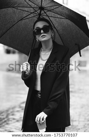 Young girl makes emotion.Dressed in a black shirt, black sweater, black hat, glasses and bright lips, fashion clothes.Wear vintage sunglasses, outfit and hat, leisure style, bright colors.Sensual woma #1753770107