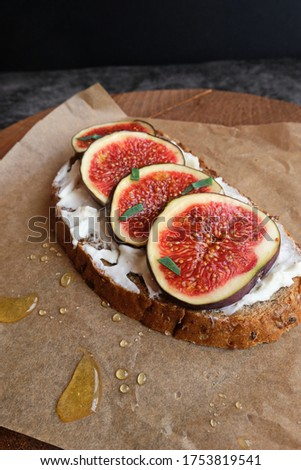 Figs. Sandwiches with figs, cheese, arugula, honey and nuts on wooden board over textured purple backdrop. Homemade. Everyday autumn kitchen. Vertical. #1753819541