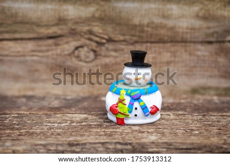 Snowman standing on the wooden board with copy space using as background or wallpaper holiday. Winter Christmas landscape concept. Merry Christmas and happy New Year greeting card. #1753913312