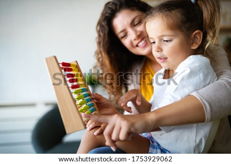 Mother and little cute girl, kid playing with abacus, early education Royalty-Free Stock Photo #1753929062
