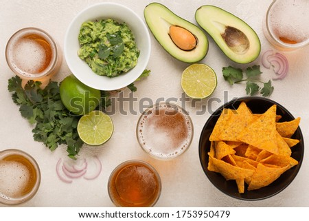 Guacamole, corn chips and beer, light Mexican snack or dinner