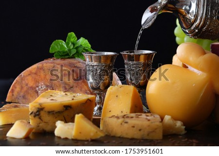 White wine is poured into a vintage metal glass . Hard cheeses in the range. Copy space. Horizontal photo on a black background. #1753951601