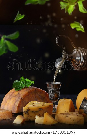 White wine is poured into a vintage metal glass . Hard cheeses in the range. Copy space and levitation. Vertical photo on a black background.Macro photo #1753951997