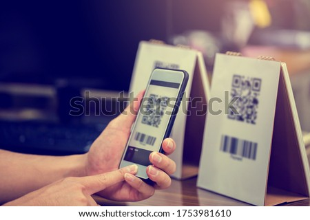 Closeup of a hand holding phone and scanning qr code. Man hand paying with qr code. Customer hand making payment through smart phone and scan code. Selective focus. #1753981610