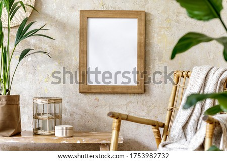 Neutral composition of living room interior with mock up picture frame, rattan armchair, a lot of tropical plants in design pots, decoration and elegant personal accessories in stylish home decor.