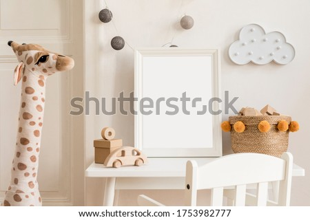 Modern and design scandinavian interior of kidroom with white desk, armachirs, mock up poster frame, natural basket, teddy bear, plush toys and cute children's accessories.  Royalty-Free Stock Photo #1753982777