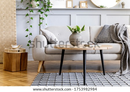 Scandinavian concept of living room interior with design sofa, coffee table, plant in pot, lamp, carpet, plaid, pillow, shelf, decoration and personal accessories in modern home staging. Royalty-Free Stock Photo #1753982984