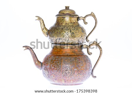 Isolated antique engraved copper Turkish teapot with double stacked kettles allowing tea to be brewed in one while hot water from the larger kettle is used to dilute individual cups of tea to taste