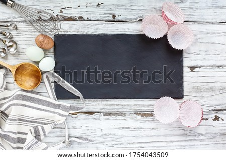 Blank slate sign with cupcake liners, apron, whisk, measuring spoons, old wooden spoon and eggs over a white wood background. Image shot from top view. Free space for text.