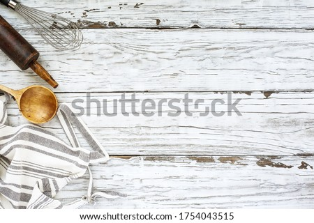 White wood baking supplies background with old wooden spoon, apron and vintage rolling pin over a white wood table. Image shot from top view. Free space for text.