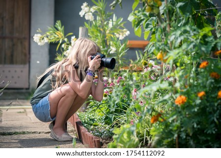 adorable blond girl taking pictures of nature with lense camera