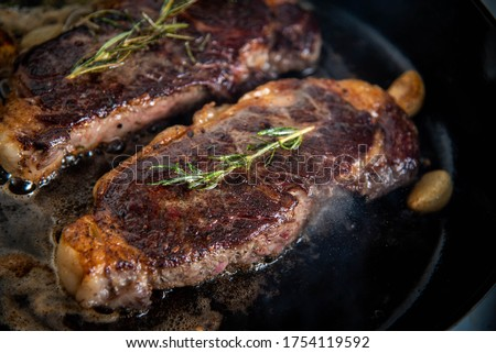 cooking new york strip steak on skillet pan Royalty-Free Stock Photo #1754119592