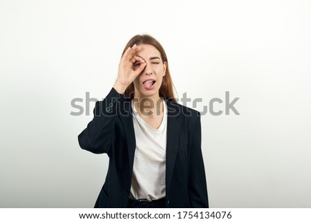 View of hand fingers showing ok sign, gesturing making okay, human emotions, facial expressions, feelings. Fooling around outside, sticks out tongue. young attractive woman with brown hair