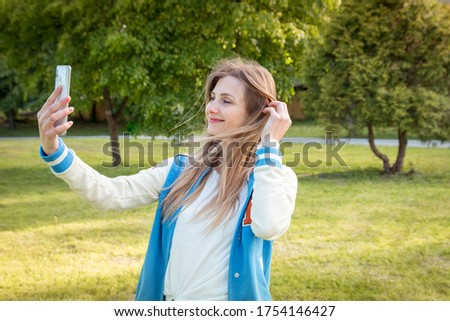 Young beautiful girl takes pictures of herself with a smartphone. The woman is in the park, the street is sunny and warm. Great summer weather