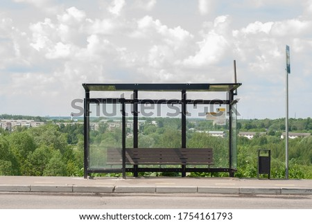 Empty public transport stop in summer. Self-isolation. Bus and minibus stops. Glass stop with a bench and a trash can. Stop without people, without passengers. bus stop sign Royalty-Free Stock Photo #1754161793