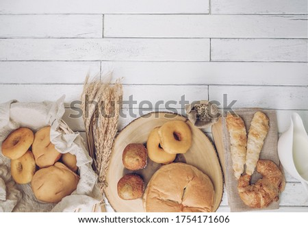 Top view of fresh fragrant bread on cutting board on wooden table with wheat, milk and eggs. Bakery loaves of bread and buns, banana cupcakes, croissant and donut. Food concept. copy space. #1754171606