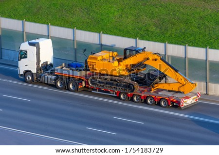 Heavy new yellow excavator on transportation truck with long trailer platform on the highway in the city Royalty-Free Stock Photo #1754183729