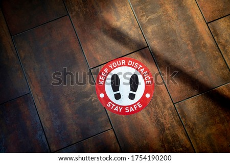Floor sign on wood floor at business stating Social Distancing Stay Safe with shoes as graphic