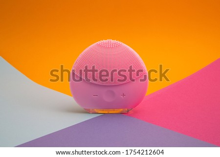 Front side of a mini magenta silicone vibrating facial cleansing brush on colorful background, close up with copy space