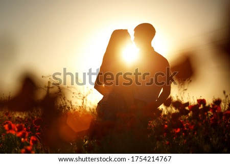 A happy couple silhouette in a poppy field in the rays of the setting sun hugging . The concept of romantic relationships