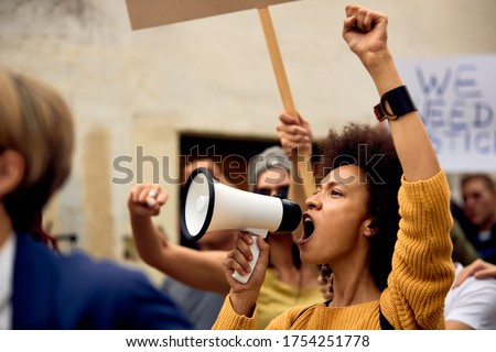 Young African American woman with raised fist shouting through megaphone while being on anti-racism protest.  Royalty-Free Stock Photo #1754251778