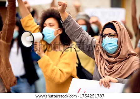 Muslim woman wearing protective face mask and supporting anti-racism movement with group of people on city streets.  Royalty-Free Stock Photo #1754251787