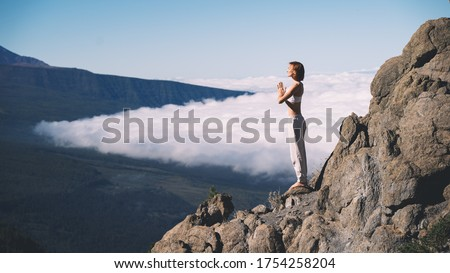 Woman enjoying nature. Female doing the yoga pose on background of natural landscape of mountains and sky. Mount Teide, volcano on Tenerife, Spain, Europe. Concept of vitality, zen energy, meditation. #1754258204