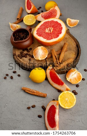 sliced fruits citrus tangerines grapefruits and lemons along with coffee seeds and brown cinnamon on the grey floor #1754263706