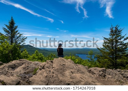 Young woman sitting at the summit of the mount-Chauve and admiring the beautiful view over the mont-Orford national park, in Quebec, Canada #1754267018