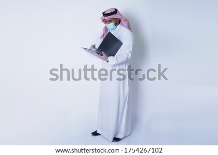 Saudi Arab man wearing mask and gloves working and writing on file