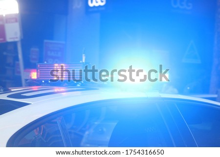 Flashing emergency lights at night. They are blue and on the top of a nsw police vehicle.  Royalty-Free Stock Photo #1754316650