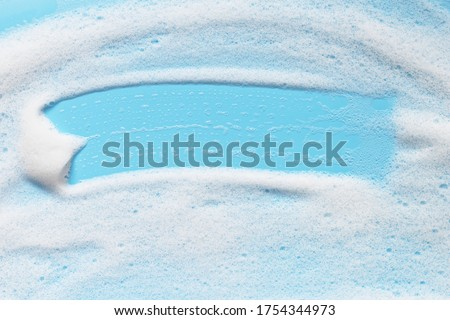 Soap foam on blue surface. Shampoo, shower gel, mousse bubbles.  Bath hygiene background. Abstract cleansing foam texture #1754344973